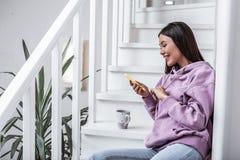 Apelar a mulher à moda que senta-se sobre protagoniza em sua casa da casa de campo imagem de stock royalty free