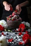 Apelmácese con el chocolate que adorna con la fresa y las flores Fotografía de archivo