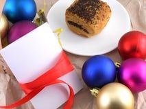 Apelmácese con las bolas de la Navidad y la tarjeta blanca de la invitación Foto de archivo