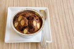 Apelmace el brownie del chocolate en una taza de la hoja en la tabla de madera foto de archivo