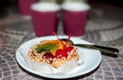 Apelmace la cesta con la crema, adornada con las rebanadas de kiwi, de piña y de dos cerezas, foco selectivo Imagen de archivo libre de regalías