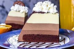 Apelmace la crema batida tres chocolates, rebanada de torta en la placa Fotografía de archivo libre de regalías