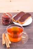 Apelmaza eclairs, y una taza de té con canela Fotografía de archivo libre de regalías