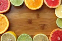 Apelsin-, citron-, grapefrukt- och limefrukthalvaskivor på träbräde med kopieringsutrymme Blandning av den skivade bästa sikten f Royaltyfria Foton