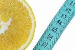 Apelsin e centimetro, un simbolo della dieta e cibo sano fotografia stock