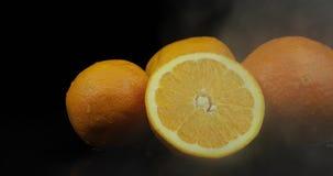 Apelsin för tropisk frukt i kalla ismoln av dimmarök på svart bakgrund stock video