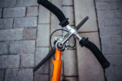 Apelsin fixad kugghjulcykel på en grå trottoar Royaltyfria Foton