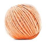 Apelsin flätad clew som sticker trådrulle som isoleras på vit bakgrund Arkivfoto
