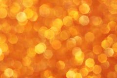 Apelsin guling, guld- gnistrandebakgrund Fotografering för Bildbyråer