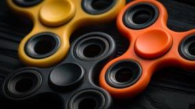 Apelsin-, guling- och svartspinnare på en svart bakgrund Royaltyfri Foto