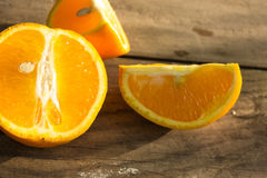 Apelsin, halva av apelsinen, orange lobule och korg med apelsiner Arkivbilder