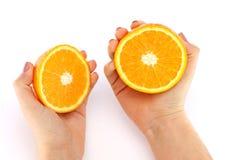 Apelsin i ett snitt i hans händer Arkivfoton