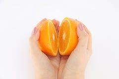 Apelsin i ett snitt i hans händer Arkivfoto