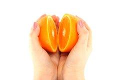 Apelsin i ett snitt i hans händer Royaltyfri Fotografi