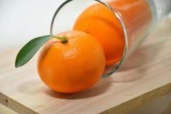 Apelsin i exponeringsglas på den wood tabellen Fotografering för Bildbyråer