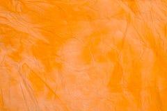 Apelsin knövlad färgad textur för bakgrund för silkespapperpapper Royaltyfri Illustrationer