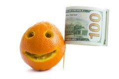 Apelsin med ett leende och en flagga av amerikanen hundra dollarräkningar Begreppet av Amerika, prishöjningdollar Isolerat på vit royaltyfri foto