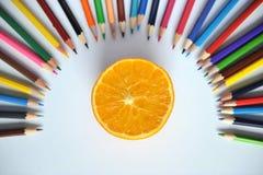 Apelsin med kulöra blyertspennor och shavings på en vit bakgrund arkivfoton
