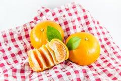 Apelsin med segment på ginghamtyg Arkivbild