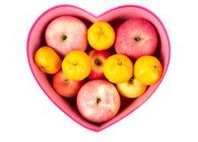 Apelsin och äpple som är blandade i hjärta-formad gåvaask på vit Arkivfoto
