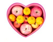 Apelsin och äpple som är blandade i hjärta-formad gåvaask på vit Fotografering för Bildbyråer