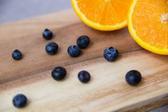 Apelsin och blåbär på träskärbräda arkivbild