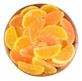 Apelsin- och citrongodisskivor i en träbunke på en vit Arkivbilder
