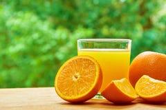 Apelsin och exponeringsglas på tabellen Arkivbild