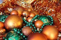 Apelsin- och gräsplanjulbollar och glitter Arkivfoto