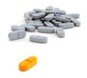 Apelsin- och grå färgpreventivpillerar på vit Royaltyfria Bilder