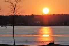 Apelsin och gulingsolnedgång över den djupfrysta sjön Arkivbild