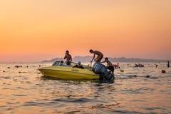 Apelsin och gulingsolnedgång med folk i en förtöjd motorbåt mot horisonten arkivfoton