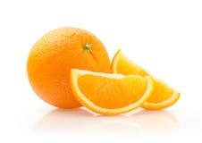 Apelsin och skivor på vit bakgrund Arkivbild
