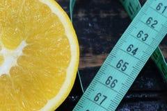 Apelsin y centímetro, un símbolo de la dieta y consumición sana imagen de archivo libre de regalías