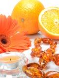 Apelsinen anmärker på en vit bakgrund: en orange gerberablomma, en bärnsten pryder med pärlor och stearinljuset - stilleben Arkivbilder