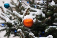 Apelsinen blå garnering klumpa ihop sig på ett snö täckt prydligt träd Royaltyfri Foto