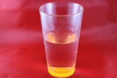 Apelsinen färgad botten av att dricka exponeringsglas skapar optisk illusion, med röd bakgrund Royaltyfri Foto