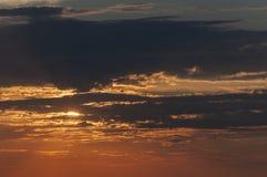 Apelsinen fördunklar under solnedgången Arkivbild