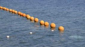 Apelsinen håller flytande på ett rep i havet Fäkta för att simma i havet stock video