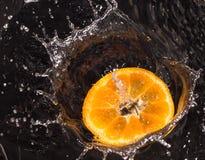 Apelsinen i vatten plaskar på en svart bakgrund Royaltyfria Bilder
