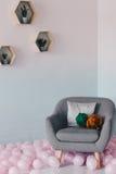 Apelsinen och gräsplanmerinoull klumpa ihop sig att ligga på en fåtölj Fotografering för Bildbyråer