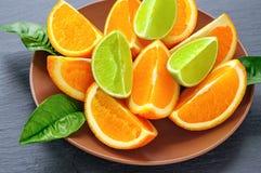 Apelsinen och limefrukt skivade segment med gröna sidor på den bruna plattan, svart kritiserar stenen Vitaminbegrepp royaltyfri bild
