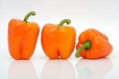 Apelsinen pepprar i en ro på vitbakgrund Arkivfoto