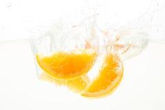 Apelsinen skivar att falla djupt under vatten med en stor färgstänk Royaltyfri Bild