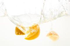 Apelsinen skivar att falla djupt under vatten med en stor färgstänk Arkivbild