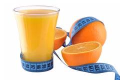 Apelsiner exponeringsglas av orange fruktsaft och mätaband Arkivfoton