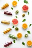 Apelsiner, grapefrukter, kiwi och fruktsafter på gul bakgrund sunt begrepp royaltyfri foto