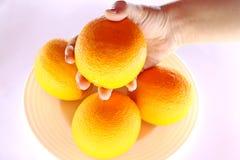 Apelsiner i bunke och hand från över Royaltyfri Foto