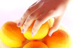 Apelsiner i bunke och hand från över Royaltyfri Bild