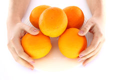 Apelsiner i bunke och hand med dem Arkivfoto